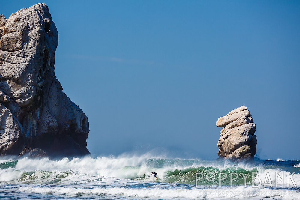A surfer catches a wave by Morro Rock in Morro Bay, California