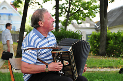 "Playing for the summer crowds along the Volga River, a musician brightens the afternoon in Uglich, Russia. As one of Russia's ""Golden Ring"" cities, Uglich is designated a town of significant cultural importance."