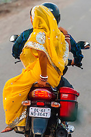 A couple on a motorcycle on the Ring Road in Delhi, India.