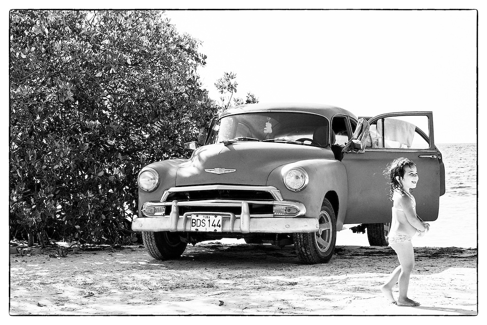Old car with little girl, in front of the sea on the beach. Cayo Jutias, Cuba.