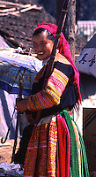 A flower Hmong woman carrying sugar cane at a market in Northern Vietnam.