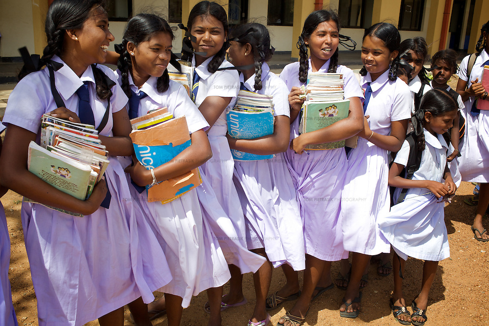 Students at the end of the day for those at Palchenai school. <br /> <br /> The UNICEF- built Palchenai school educates 581 pupils 1-12 Grade. The original Palchenai school building was badly damaged by the tsunami and eleven students lost their lives. UNICEF provided four semi-permanent teaching buildings during the transition period before the new school building was constructed. Work on this building began in 2006 but was halted later that year when a local escalation in the Sri Lankan conflict forced the entire community served by the school to relocate their homes. Most had returned back by early 2007 when the school again began teaching. The new school building constructed by UNICEF was opened in June 2008. UNICEF provides teacher training in Child Friendly Schooling.<br /> <br /> Photo: Tom Pietrasik<br /> Batticaloa District, Sri Lanka<br /> October 1st 2009