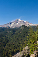 """Mount Rainier and the Nisqually Valley in Mount Rainier National Park, Washington State, USA.  Photographed from Ricksecker Point near the Paradise area of Rainier.  The """"clouds"""" on Rainier appear to be dust blowing off the peak's surface."""