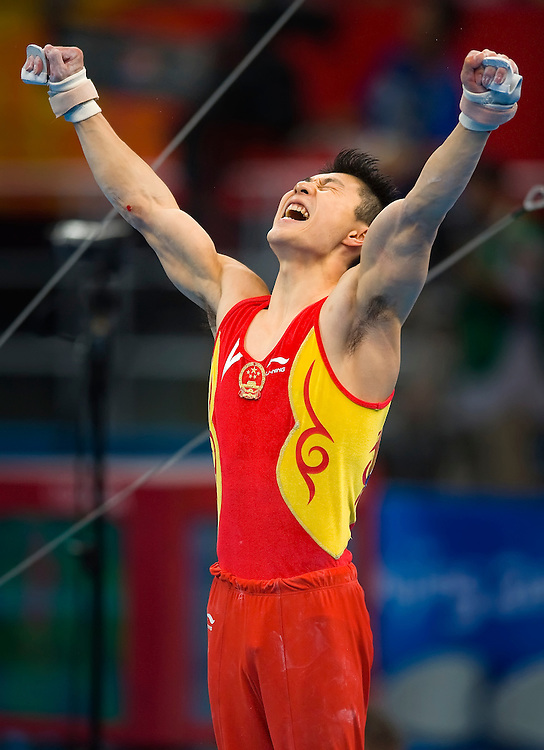 Chinese gymnast Xiaopeng Li reacted after his high bar dismount in the final appartus of the men's gymnastics team final August 12, 2008 at the National Indoor Stadium during the 2008 Summer Olympic Games in Beijing, China. China won the overall gold medal, Japan the silver and the United States the bronze. (photo by David Eulitt/MCT)