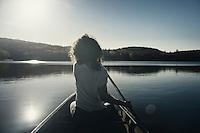 Young woman canoeing on a lake in fall. Muskoka, Ontario, Canada.