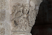 Carved capital with interlacing design, palm leaves and human heads, in the Abbatiale Sainte-Foy de Conques or Abbey-church of Saint-Foy, Conques, Aveyron, Midi-Pyrenees, France, a Romanesque abbey church begun 1050 under abbot Odolric to house the remains of St Foy, a 4th century female martyr. The church is on the pilgrimage route to Santiago da Compostela, and is listed as a historic monument and a UNESCO World Heritage Site. Picture by Manuel Cohen