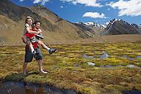 Man giving woman piggy-back ride through pond near mountains