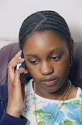 Teenage girl using mobile phone; looking sad,