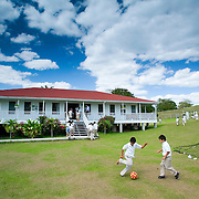 Young boys playing football (soccer) infront of school house, Gallon Jug School, Orange Walk, Belize