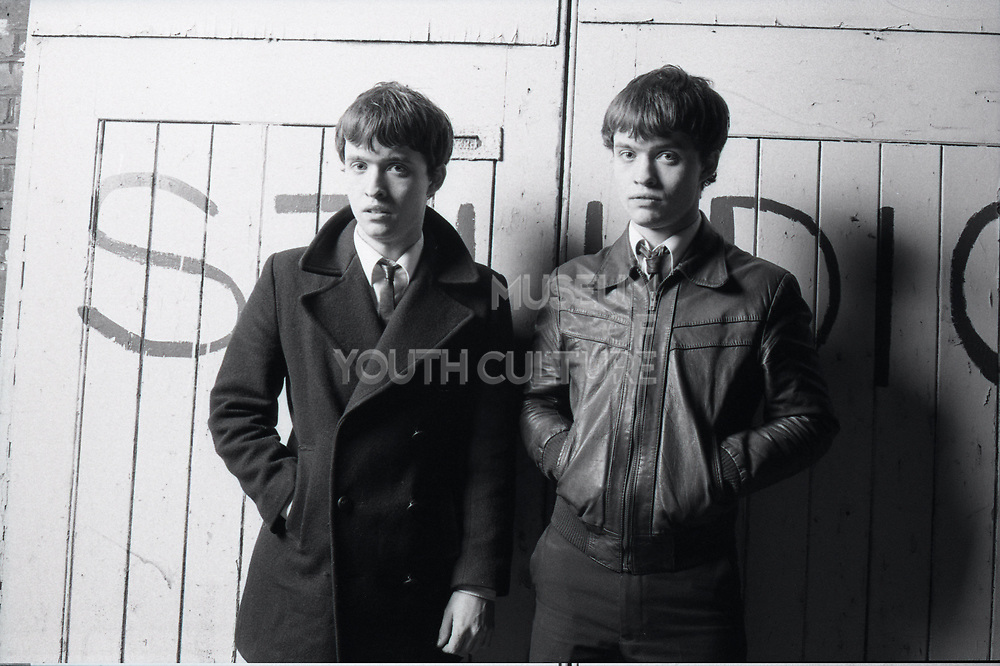 Two members of the band The Bishops standing in front of a wall with studio written on it.