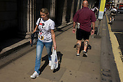 A man with Laurel and Hardy tattooes walks along a City of London street, passing a woman with Mickey Mouse on her T-shirt.
