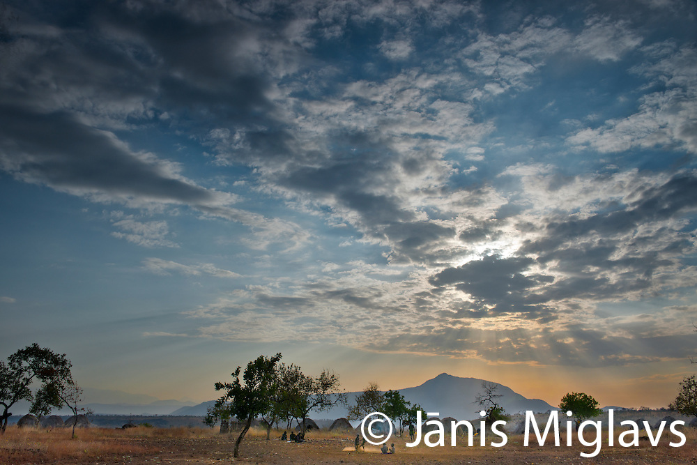 Sunrise clouds over Belle, a Mursi tribe village in front of mountain in Mago National Park, Omo Valley, Ethiopia, Africa.