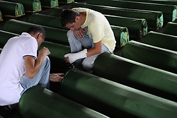 60104827  <br /> Two men mourn beside remains of 409 newly identified victims of Srebrenica Massacre in Memorial Centre Potocari , near by Srebrenica, Bosnia-Herzegovina, on July 10, 2013. A huge funeral will be held on July 11. More than 7,000 Bosnian Muslim men and boys were massacred in Srebrenica in July 1995 by Bosnian Serb forces and a paramilitary unit from Serbia, picture taken Wednesday, July 10, 2013.<br /> Photo by imago / i-Images