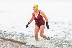 © Licensed to London News Pictures. 17/03/2019. Brighton, UK. Members of the Brighton Swimming Club take to the sea in Brighton and Hove as milder weather hits Brighton and the South Coast. Photo credit: Hugo Michiels/LNP