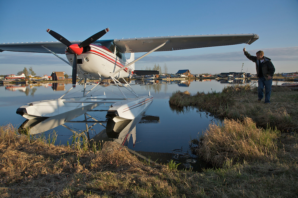 Lake Hood float plane facility, Anchorage, Alaska.  Peter Grunwaldt, private pilot,prepares plane for flight in early morning.