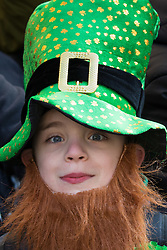 "London, March 13th 2016. The annual St Patrick's Day Parade takes place in the Capital with various groups from the Irish community as well as contingents from other ethnicities taking part in a procession from Green Park to Trafalgar Square.  PICTURED: A young ""leprechaun"" watches the parade. ©Paul Davey<br /> FOR LICENCING CONTACT: Paul Davey +44 (0) 7966 016 296 paul@pauldaveycreative.co.uk"