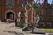 American lady stands for a souvenir photo on the Olympic rings that stand at the entrance of King Henry the Eighth's Hampton Court Palace on the first day of competition of the London 2012 Olympic 250km mens' road race. Starting from central London and passing the capital's famous landmarks before heading out into rural England to the gruelling Box Hill in the county of Surrey. Local southwest Londoners lined the route hoping for British favourite Mark Cavendish to win Team GB first medal but were eventually disappointed when Kazakhstan's Alexandre Vinokourov eventually won gold.