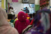 A teacher leading a session at a cafe meeting organised for and hosted by Awaj Foundation, Dhaka, Bangladesh.<br /> <br /> Awaj Foundation was founded by Nazma Akter in 2003 to support and empower garment workers to negotiate safer and fairer working conditions in factories.