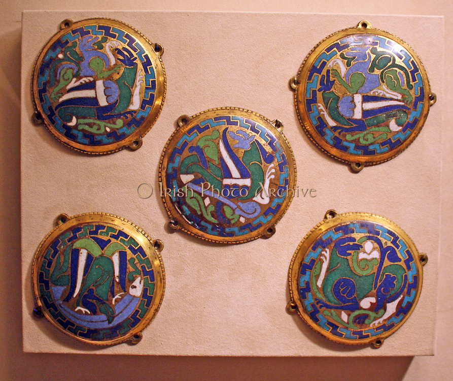 Five Medallions from a Coffret.  Champleve enamel on gilded copper.  French, Conques.  Made about 1110-30  The blue and green beasts, locked in battle and compressed into these circular medallions are emblematic of goldsmiths' work created at Conques under the patronage of Abbot Boniface.