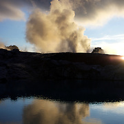 A spectacular geyser at sunset at Te Puia, Rotorua. Te Puia is the premier Maori cultural centre in New Zealand - a place of gushing waters, steaming vents, boiling mud pools and spectacular geysers. Te Puia also hosts National Carving and Weaving Schools and  daily maori culture performances including dancing and singing. Rotorua, 8th December 2010 New Zealand.  Photo Tim Clayton.