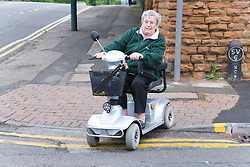 Older woman navigating a road kerb in an electric mobility scooter,