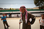 A village elder walks towards demonstrators at an anti-government protest in Basheria, Idlib, Syria on Friday 15th June 2012. The weekly demonstrations call for the regime to step down, killings to end, and for democratic change in Syria. Basheria, Idlib, Syria. 15/06/2012