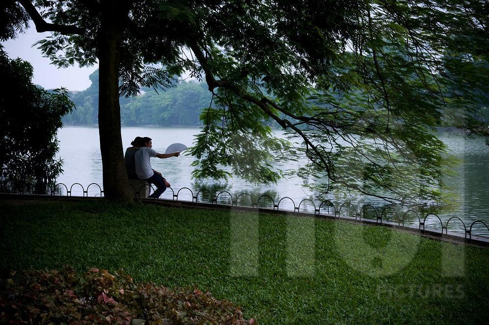 Young vietnamese couple contemplate waters of Hoan kiem lake, Hanoi, Vietnam, Southeast Asia
