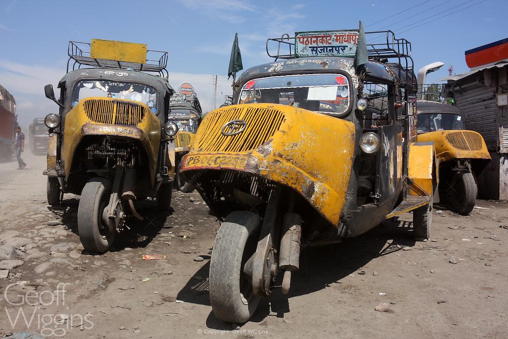 Vintage three wheeler Bajaj Tempo taxi buses await business in Jammu, northern India.