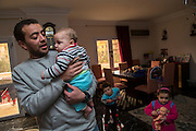 CAIRO, EGYPT - FEBRUARY 25: Al Jazeera English (AJE) producer Baher Mohamed (l) holds his infant son Haroun (2nd from left), as son Hazem and daughter Fairouz play nearby  February 25, 2015 at his family apartment in the Sheikh Zayed district on the outskirts of Cairo, Egypt. Haroun was born while Baher was being detained in an Egyptian prison for more than 12 months last year.  (Photo by Scott Nelson, for the Washington Post)