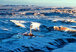 Stock aerial photo of an oil and gas drilling rig surrounded by snow in the Missouri Breaks of Montana USA