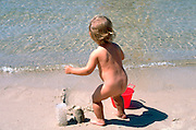 Toddler playing with the sand on the beach age 2.  Cedarville Michigan USA