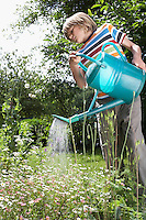 Young boy (7-9) watering flowers in garden