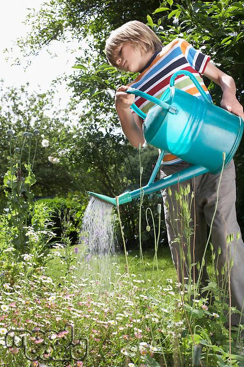 Young boy (7-9) watering flowers in garden