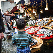 A young boy looks at the fish for sale at the Karakoy Fish Market in Istanbul near the Galata Bridge.