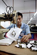 30 March 2006 - Dongguan, Guangdong Province - A factory worker sews a bag in a handbad factory.