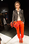 Bright orange trousers, a matching bag in soft leather and a black leather jacket with wide lapels. By Monika Chiang at Spring 2013 Fashion Week in New York.