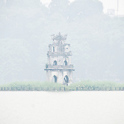 Turtle Tower (Thap Rua), on a small island in the middle of Hoan Kiem Lake in the heart of Hanoi is partially obscured by a thick morning fog.