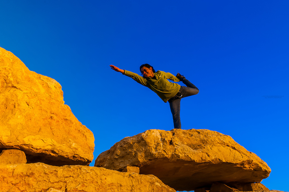 Woman doing a yoga pose atop a rock sculpture in the sculpture garden, Mitze Ramon, Negev Desert, Israel.