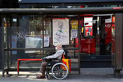© Licensed to London News Pictures. 12/04/2020. London, UK.  A man in a wheelchair wearing a face mask waits at a bus stop in north London. Coronavirus lockdown continues to slow the spread of COVID-19 and reduce pressure on the NHS. Over 10,000 people in the UK have died in hospitals due to coronavirus. Photo credit: Dinendra Haria/LNP