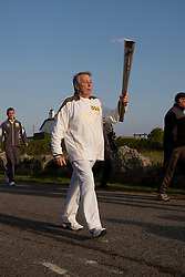 © Licensed to London News Pictures. 19/05/2012. Lands End, UK. Eric Smith carries the Olympic Flame out of Lands End ahead of its 8,000 mile journey across the UK. Photo credit : Ashley Hugo/LNP