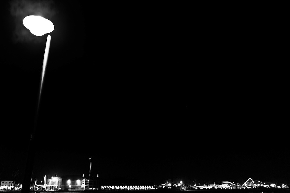 Santa Cruz Boardwalk at night, as seen from Santa Cruz Pier, in Santa Cruz, CA.  Copyright 2014 Reid McNally.