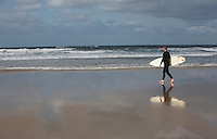 Man carrying surfboard walking on beach