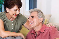 Middle-aged couple sitting smiling looking into eyes