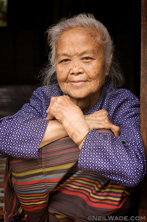A elderly village shows signs of hard work in her heavily arthritic hands as she takes a rest in her doorway in Muang Khao.