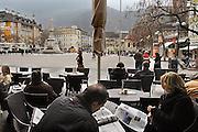 Italie, Bolzano, 8-3-2008..Een man en een vrouw lezen op het terras van een café in het centrum van de stad. De man een italiaanstalige krant, de vrouw een duitstalig tijdschrift. Bolzano, Bozen, is na de eerste wereldoorlog bij Italië gevoegd en is tweetalig. De bevolking is sterk gericht op Oostenrijk...Foto: Flip Franssen