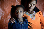 "Belanesh's daughter (left), age 10, and Belanesh, 25, live in a shack, inside red light district. The woman by the need is forced as a sex workers. When she was still a teenager, she escaped from her village after a few years of marriage with a man much older. Addis Ababa, Ethiopia, on thursday, Febrary 19 2009.....In a tangled mingling of tradition and culture, in the normal place of living, in a laid-back attitude. The background of Ethiopia's ""child brides"", a country which has the distinction of having highest percentage in the practice of early marriages despite having a law that establishes 18 years as minimum age to get married. Celebrations that last days, their minds clouded by girls cups of tella and the unknown for the future. White bridal veil frame their faces expressive of small defenseless creatures, who at the age ranging from three to twelve years shall be given to young brides men adults already...To protect the identities of the recorded subjects names and specific places are fictional."
