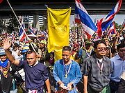 """20 DECEMBER 2013 - BANGKOK, THAILAND:   Anti-government protestors march down Silom Road. Thousands of anti-government protestors, supporters of the so called Peoples Democratic Reform Committee (PRDC), jammed the Silom area, the """"Wall Street"""" of Bangkok, Friday as a part of the ongoing protests against the caretaker government of Yingluck Shinawatra. Yingluck dissolved the Thai Parliament earlier this month and called for national elections on Feb. 2, 2014. The protestors want the elections postponed and the caretaker government to step down. The Thai election commission ruled Friday that the election would go on dispite the protests.        PHOTO BY JACK KURTZ"""