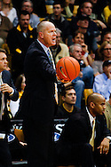 November 24th, 2013:  Colorado Buffaloes head coach Tad Boyle holds the ball out for the officials in the second half of the NCAA Basketball game between the Harvard Crimson and the University of Colorado Buffaloes at the Coors Events Center in Boulder, Colorado