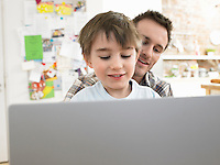 Boy (3-6) using laptop with father at home