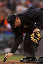 July 23, 2011; San Francisco, CA, USA;  MLB umpire Sam Holbrook (34) brushes off home plate during the seventh inning between the San Francisco Giants and the Milwaukee Brewers at AT&T Park. San Francisco defeated Milwaukee 4-2.